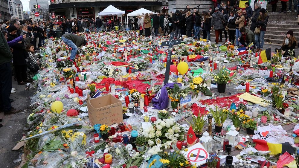 BRUSSELS, BELGIUM - MARCH 27:  People place flowers and candles in the Place de la Bourse to pay tribute to the 31 victims of the attacks in Brussels last week on March 27, 2016 in Brussels, Belgium. The peaceful gathering in the Place de la Bourse was disrupted by right-wing protesters in what is believed to be a demonstration in reaction to last week's terrorist attacks in Brussels. The protest was later dispersed by riot police using water cannons. (Photo by Sylvain Lefevre/Getty Images)