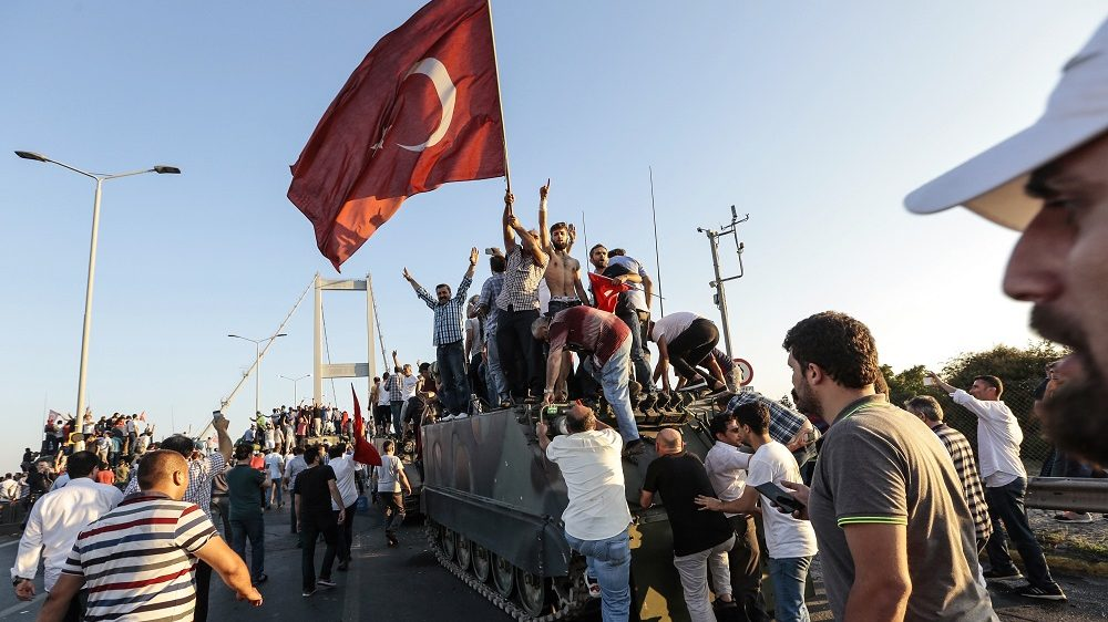 ISTANBUL, TURKEY - JULY 16: Supporters of Turkish President Recep Tayyip Erdogan wave flags as they capture a Turkish Army APC after soldiers involved in the coup attempt  have surrendered on Istanbul's Bosphorus bridge in Istanbul, July 16, 2016 Turkey. Istanbul's bridges across the Bosphorus, the strait separating the European and Asian sides of the city, have been closed to traffic.Turkish President Recep Tayyip Erdogan has denounced an army coup attempt, that has left atleast 90 dead 1154 injured in overnight clashes in Istanbul and Ankara. (Photo by Gokhan Tan/Getty Images)