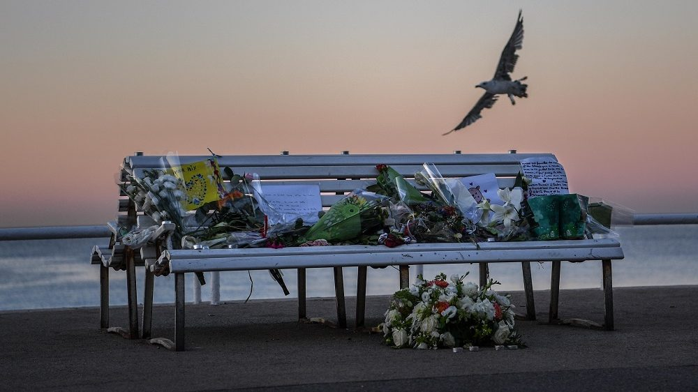 NICE, FRANCE - JULY 17:  A tribute is laid on a bench where a person was killed on the Promenade des Anglais on July 17, 2016 in Nice, France. Six people believed to be linked to the man who killed 84 people in Nice are in police custody according to a statement by the Paris prosecutor's office after a French-Tunisian attacker killed 84 as he drove a lorry through crowds, gathered to watch a firework display during Bastille Day Celebrations. The attacker then opened fire on people in the crowd before being shot dead by police  (Photo by David Ramos/Getty Images)