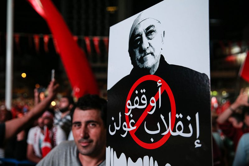 """ISTANBUL, TURKEY - JULY 20: A man holds a placard reading in """"Take your hands of Turkish democracy"""" with the portrait of Fethullah Gulen in front of Turkish President Recep Tayyip Erdogan's residence in Kisikli as they protest against Parallel State/Gulenist Terrorist Organization's failed military coup attempt in Istanbul, Turkey on July 20, 2016. Berk Ozkan / Anadolu Agency"""