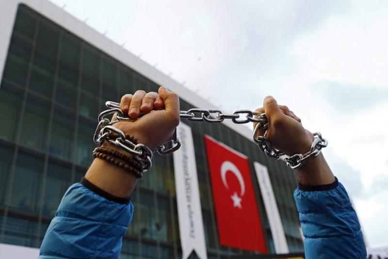 Isztambul, 2016. március 5. Egy fémlánccal összekötözött csuklójú tüntetõ az ellenzéki Zaman médiacsoport szerkesztõségének épülete elõtt Isztambulban 2016. március 4-én. A több száz demonstráló amiatt tiltakozott, hogy egy bírósági döntés értelmében a lap igazgatását az állam által kinevezett tagokból álló felügyeletre bízták, s ez sokak szerint a Zaman állami ellenõrzés alá helyezését jelenti. A napi 850 ezres példányszámban megjelenõ lap Törökország egyik legnagyobb példányszámú újságja, és a hozzá kapcsolódó médiumok a Recep Tayyip Erdogan török elnök legnagyobb politikai ellenfelének számító Fethullah Gülen iszlám hitszónok érdekeltségébe tartoznak. (MTI/EPA/Turgut Engin)