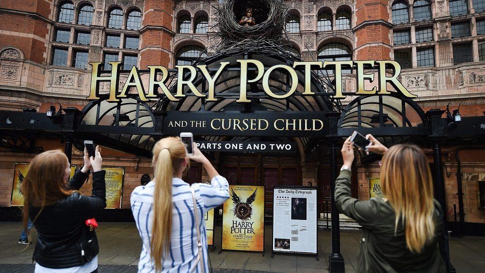 London, 2016. július 29. Rajongók felvételt készítenek a Harry Potter és az elátkozott gyermek címû színházi elõadást hirdetõ feliratról a londoni Palace színház bejáratánál 2016. július 29-én, egy nappal a világhírû fantasy regénysorozat folytatásának színházi õsbemutatója elõtt.  (MTI/EPA/Andy Rain)