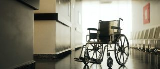 Standard manual wheelchair standing in empty hospital corridor