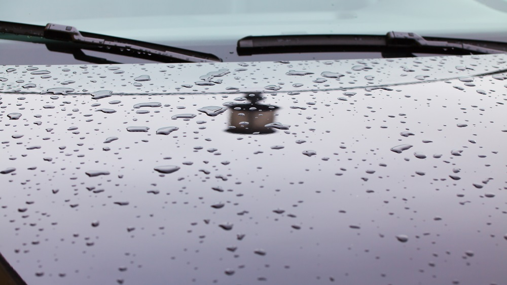 Reflection of the street lamp and raindrops on the hood of the car in the parking lot.