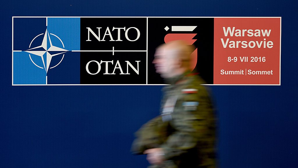 A Polish soldier walking past a sign for the Nato summit, in the grounds of the national stadium inWarsaw, Poland, 7 July 2016. The state and government leaders of NATO are meeting in Warsaw on 08 and 09 July 2016 to discuss their strategy of deterrence against Russia. Photo:RAINERJENSEN/dpa