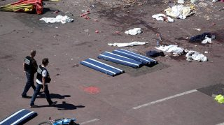"""Policemen walk on the site where a truck drove into a crowd watching a fireworks display on the Promenade des Anglais seafront in the French Riviera town of Nice on July 15, 2016.An attack in Nice where a man rammed a truck into a crowd of people left 84 dead and another 18 in a """"critical condition"""", interior ministry spokesman Pierre-Henry Brandet said Friday. An unidentified gunman barrelled the truck two kilometres (1.3 miles) through a crowd that had been enjoying a fireworks display for France's national day before being shot dead by police. / AFP PHOTO / Valery HACHE"""