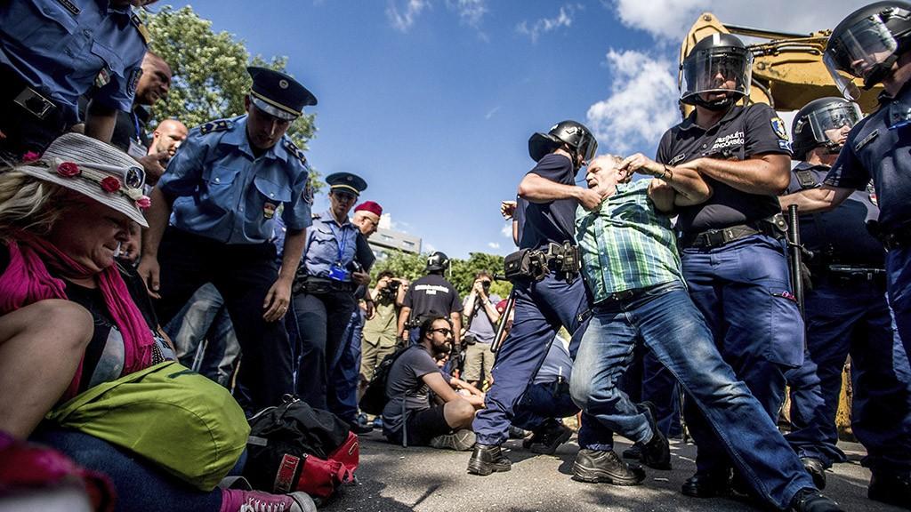 Budapest, 2016. június 28.Rendőrök vezetik el a Ligetvédők nevű civil mozgalom egyik aktivistáját a Közlekedési Múzeumnál zajló építkezésnél tartott demonstráció során 2016. június 28-án. A rendőrök több mint harminc tüntetőt vezettek ki a demonstráció helyszínéről, egy embert előállítottak, miután a tüntetők egy csoportja áttörte az építkezési kordont és bement az építési területre.MTI Fotó: Balogh Zoltán