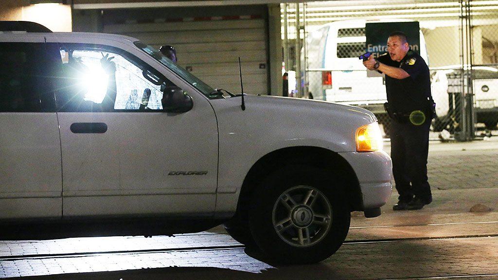 Dallas, 2016. július 8.Fegyvert fog egy vezetőre egy rendőr, miután két férfi tüzet nyitott társaira az amerikai rendőri túlkapások elleni tüntetésen a Texas állambeli Dallasban 2016. július 7-én éjjel. A zavargásba torkollt tiltakozáson négy rendőrt agyonlőttek, hetet pedig megsebesítettek. Július 5-én a louisianai Baton Rouge-ban, majd két nappal később a minnesotai Falcon Heightsban rendőrök intézkedés közben lelőttek egy fegyvertelen férfit. A lelőtt férfiak mindkét esetben afroamerikaiak, a rendőrök fehérek voltak. (MTI/AP/L.M. Otero)