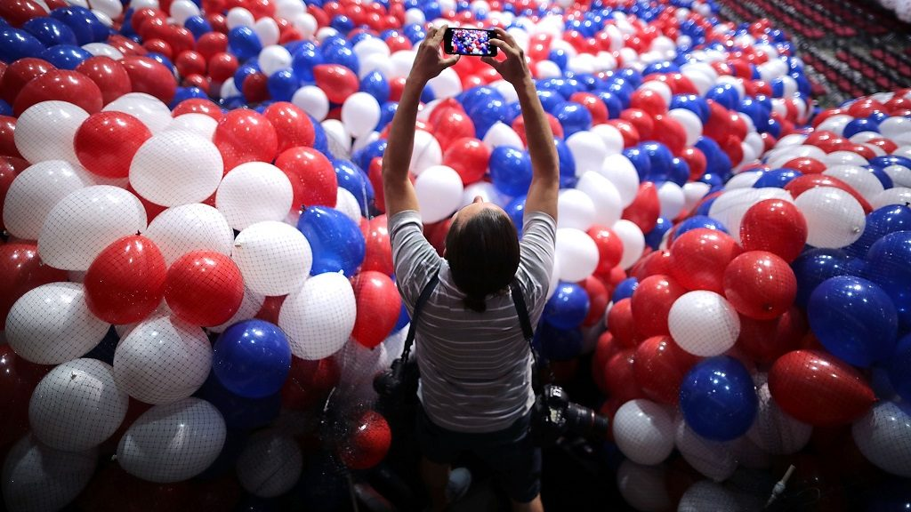 CLEVELAND, OH - JULY 15:  A news photographer makes images of nets filled with thousands of red, white and blue balloons before they are lifted into the ceiling of the Quicken Loans Arena July 15, 2016 in Cleveland, Ohio.The Republican National Convention is scheduled to begin on Monday.  (Photo by Chip Somodevilla/Getty Images)