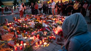 MUNICH, GERMANY - JULY 23:  People mourn near the crime scene at OEZ shopping center the day after a shooting spree left nine victims dead on July 23, 2016 in Munich, Germany. According to police an 18-year-old German man of Iranian descent shot nine people dead and wounded at least 16 before he shot himself in a nearby park. For hours during the spree and the following manhunt the city lay paralyzed as police ordered people to stay off the streets. Original reports of up to three attackers seem to have been unfounded. The shooter's motive is so far unclear.  (Photo by Johannes Simon/Getty Images)