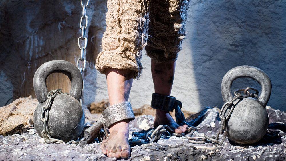 Legs in heavy iron shackles