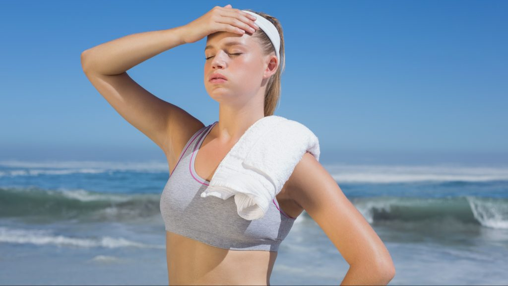 Sporty blonde standing on the beach with towel on a sunny day