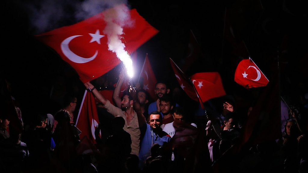 IZMIR, TURKEY - JULY 23: Citizens wave Turkish Flags as they gather at Konak Square during a demonstration, staged to protest and to show solidarity against Parallel State/Gulenist Terrorist Organization's failed military coup attempt in Izmir, Turkey on July 23, 2016. Parallel State is a terrorist organization leaded by U.S.-based cleric Fetullah Gulen, who is accused of a long-running campaign to overthrow the state through infiltrating into Turkish institutions, particularly the military, police and judiciary, forming a 'parallel state'.  Evren Atalay / Anadolu Agency