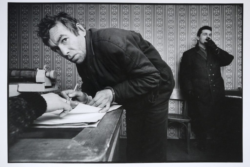 A petty thief signing his confesion at the local police station.  the arresting officer stands in the background.