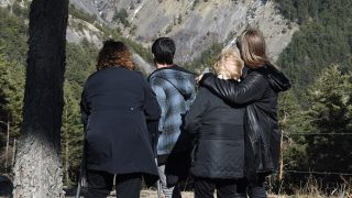 Relatives and friends of victims pay tribute at the Col Mariaud in Le Vernet, southwestern France, on March 24, 2016, in front of  the mountain were the plane of Germanwings crashed a year ago, to mark the first anniversary of the Germanwings tragedy in which a suicidal pilot crashed a plane into a mountainside, killing all 150 on board.  The ill-fated plane took off from Barcelona and was headed to Dusseldorf in Germany when German co-pilot Andreas Lubitz, 27, drove it into the ground on March 24, 2015.  / AFP PHOTO / ANNE-CHRISTINE POUJOULAT