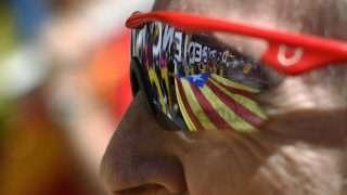 """A Catalan independence flag is reflected in the glasses of a protestor during a demonstration called by some 20 social movements, groups and organizations under the slogan, """"Rights, can't be suspended"""" outside the Catalan government headquarters in Barcelona on May 29, 2016. / AFP PHOTO / LLUIS GENE"""