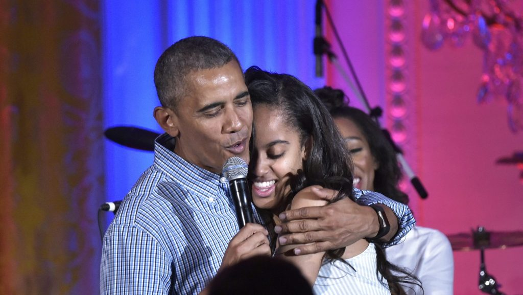 US President Barack Obama hugs his daughter Malia on her birthday during an Independence Day Celebration for military members and administration staff on July 4, 2016 in the East Room of the White House in Washington, DC. / AFP PHOTO / Mandel Ngan