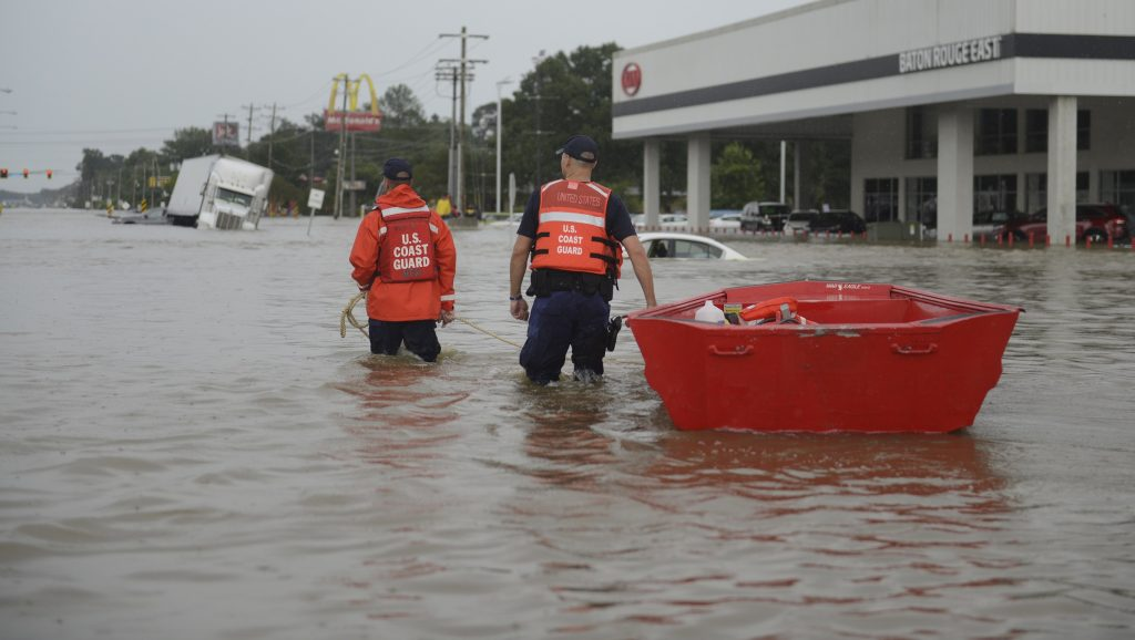 """This August 14, 2016 US Coast Guard handout photo shows Coast Guard personel bringing in a boat to evacuate residents from floodwaters in Baton Rouge, Louisiana.  Emergency crews in flood-devastated Louisiana have rescued more than 20,000 people after catastrophic inundations that left at least five dead, news reports said August 15. As many as 10,000 people are living in shelters after a weekend of torrential rains that has prompted the federal government to declare a disaster, according to Louisiana governor John Bel Edwards.  / AFP PHOTO / US Coast Guard / Petty Officer 3rd Class Brandon GILES / RESTRICTED TO EDITORIAL USE - MANDATORY CREDIT """"AFP PHOTO / US COAST GUARD / Petty Officer 3rd Class Brandon Giles"""" - NO MARKETING - NO ADVERTISING CAMPAIGNS - DISTRIBUTED AS A SERVICE TO CLIENTS"""