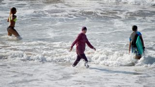 """A Moroccan woman wearing a """"burkini"""" (C), a full-body swimsuit designed for Muslim women, enters the sea at Oued Charrat beach, near the capital Rabat, on August 17, 2016. / AFP PHOTO / FADEL SENNA"""