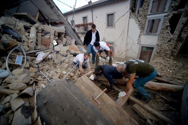 Resident search for victims in the rubble after a strong heartquake hit Amatrice on August 24, 2016.  Central Italy was struck by a powerful, 6.2-magnitude earthquake in the early hours, which has killed at least three people and devastated dozens of mountain villages. Numerous buildings had collapsed in communities close to the epicenter of the quake near the town of Norcia in the region of Umbria, witnesses told Italian media, with an increase in the death toll highly likely. / AFP PHOTO / FILIPPO MONTEFORTE