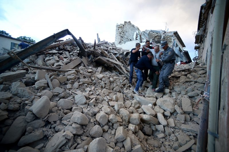 Residents and rescuers help a man among the rubble after a strong heartquake hit Amatrice on August 24, 2016 Central Italy was struck by a powerful, 6.2-magnitude earthquake in the early hours, which has killed at least three people and devastated dozens of mountain villages. Numerous buildings had collapsed in communities close to the epicenter of the quake near the town of Norcia in the region of Umbria, witnesses told Italian media, with an increase in the death toll highly likely. / AFP PHOTO / FILIPPO MONTEFORTE