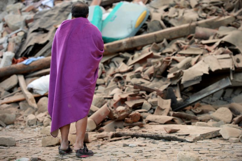 A man stands among the rubble of a house after a strong heartquake hit Amatrice on August 24, 2016. Central Italy was struck by a powerful, 6.2-magnitude earthquake in the early hours, which has killed at least three people and devastated dozens of mountain villages. Numerous buildings had collapsed in communities close to the epicenter of the quake near the town of Norcia in the region of Umbria, witnesses told Italian media, with an increase in the death toll highly likely. / AFP PHOTO / FILIPPO MONTEFORTE