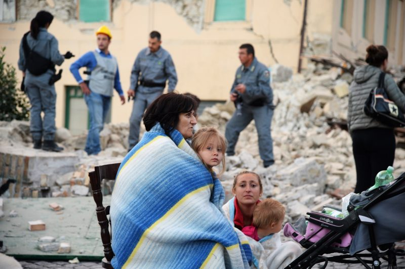 Victims sit among the rubble of a house after a strong heartquake hit Amatrice on August 24, 2016. Central Italy was struck by a powerful, 6.2-magnitude earthquake in the early hours, which has killed at least three people and devastated dozens of mountain villages. Numerous buildings had collapsed in communities close to the epicenter of the quake near the town of Norcia in the region of Umbria, witnesses told Italian media, with an increase in the death toll highly likely. / AFP PHOTO / FILIPPO MONTEFORTE