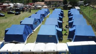 Tents of a temporary camp are installed at the central Italian village of Arquata del Tronto on August 25, 2016, a day after a 6.2-magnitude earthquake struck the region killing some 247 people. The death toll from a powerful earthquake in central Italy rose to 247 on August 25, 2016 amid fears many more corpses would be found in the rubble of devastated mountain villages. Rescuers sifted through collapsed masonry in the search for survivors, but their grim mission was clouded by uncertainty about exactly how many people had been staying in communities closest to the epicentre of the quake of August 24. / AFP PHOTO / MARCO ZEPPETELLA