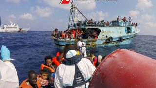 """This image grab taken from a handout video and released by the Italian Coast Guard (Guardia Costiera) on August 30, 2016, shows Italian coast guard personnel taking part in a rescue operation of a boat with migrants in the Mediterranean Sea.  Around 6,500 migrants were rescued off the coast of Libya on August 29, the Italian coastguard said, in one of its busiest days of life-saving in recent years. / AFP PHOTO / GUARDIA COSTIERA / HO / RESTRICTED TO EDITORIAL USE - MANDATORY CREDIT """"AFP PHOTO / GUARDIA COSTIERA"""" - NO MARKETING - NO ADVERTISING CAMPAIGNS - DISTRIBUTED AS A SERVICE TO CLIENTS"""