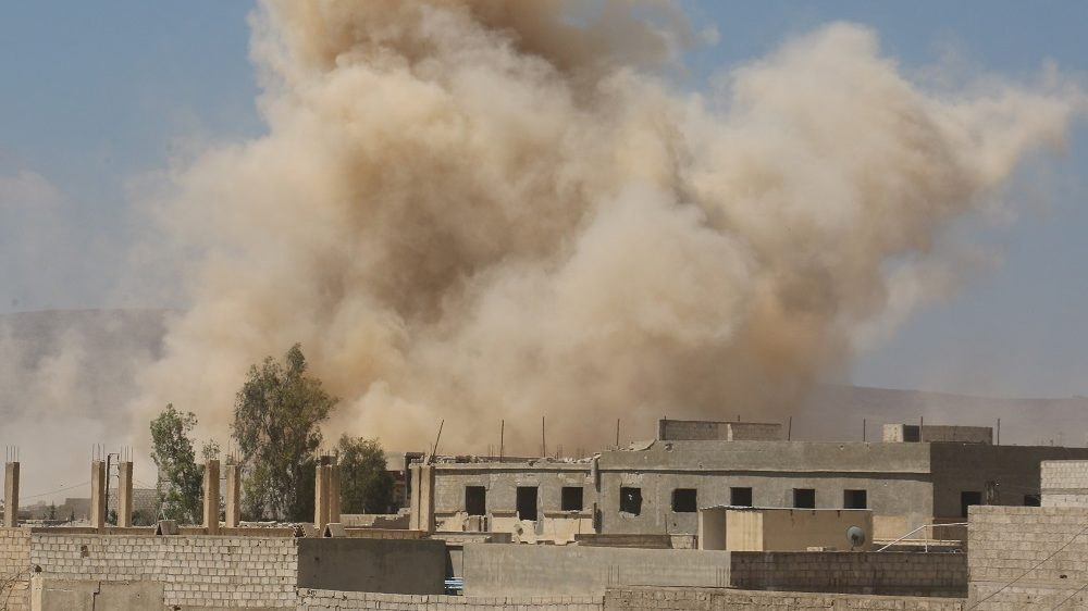 DARAYYA, SYRIA - JUNE 10: Smoke rises amid damaged buildings as the Assad regime forces carry out barrel bomb attack the opposition-controlled areas in the Darayya district in the southwest Damascus, Syria on June 10, 2016. Hussam El Ahmed / Anadolu Agency