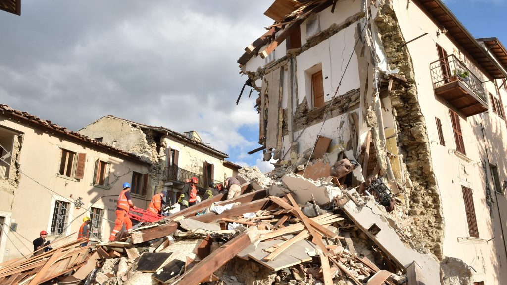 ARQUATA DEL TRONTO, ITALY - AUGUST 24:  Rescuers clear debris while searching for victims in damaged buildings on August 24, 2016 in Arquata del Tronto, Italy. Central Italy was struck by a powerful, 6.2-magnitude earthquake in the early hours, which has killed at least thirteen people and devastated dozens of mountain villages. Numerous buildings have collapsed in communities close to the epicenter of the quake near the town of Norcia in the region of Umbria, witnesses have told Italian media, with an increase in the death toll highly likely  (Photo by Giuseppe Bellini/Getty Images)