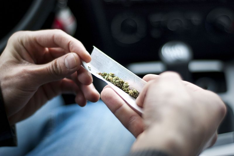 59953123 - man making joint and a stash of marijuana in the car