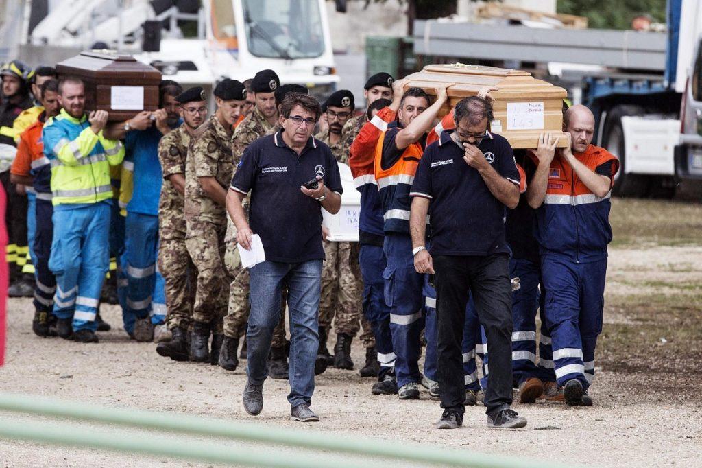 Amatrice, 2016. augusztus 30. Az augusztus 24-i közép-olaszországi földrengés áldozatainak koporsóit viszik egy mentõcsapat tagjai, valamint katonák az Amatricében tartott gyászszertartáson 2016. augusztus 30-án. A 6,2-es erõsségû földrengés miatt legalább 290 ember életét vesztette. (MTI/EPA/Roberto Salomone)