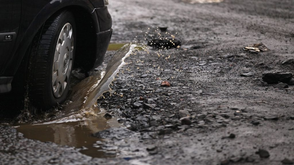 GLASGOW, SCOTLAND - MARCH 04:  A road user tries to avoid potholes on March 4, 2011 in Glasgow, Scotland. Councils across the UK are struggling to repair roads following damage caused by the coldest December since records began.  (Photo by Jeff J Mitchell/Getty Images)