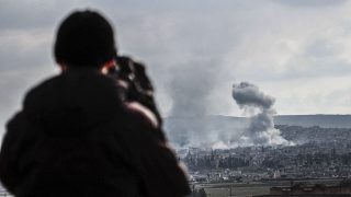 SANLIURFA, TURKEY - JANUARY 16: A photograph taken from Suruc district of Sanliurfa, Turkey, near Turkish-Syrian border crossing shows smoke rising from the Syrian border town of Kobani (Ayn al-Arab) following the US-led coalition airstrikes against the Islamic State of Iraq and the Levant (ISIL) targets on January 16, 2015. (Photo by Halil Fidan/Anadolu Agency/Getty Images)