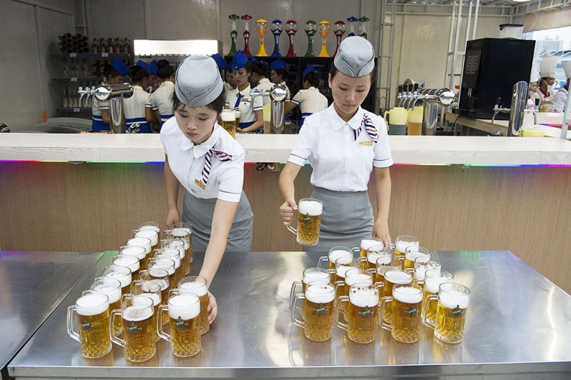 This photo taken on August 12, 2016 shows waitresses preparing jugs of beer before the opening of the Pyongyang Taedonggang Beer Festival on the banks of the Taedong river in Pyongyang. / AFP PHOTO / Kim Won-Jin