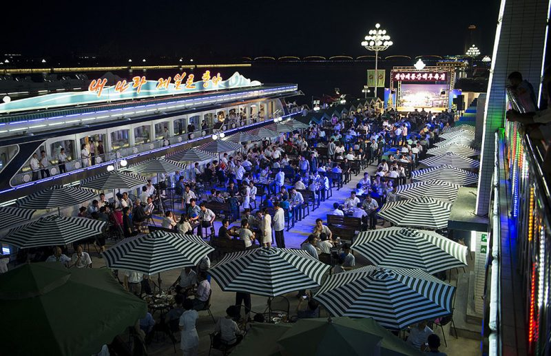 This photo taken on August 12, 2016 shows a general view of guests attending the opening of the Pyongyang Taedonggang Beer Festival on the banks of the Taedong river in Pyongyang. / AFP PHOTO / Kim Won-Jin