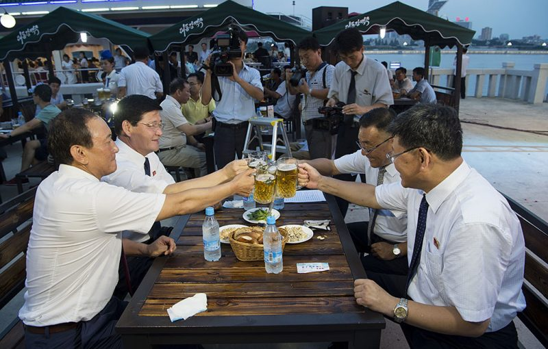 """This photo taken on August 12, 2016 shows Choe Yong Nam (L), director of the General Bureau of Public Service who doubles as chairman of the preparatory committee for the festival, saying """"cheers"""" with other officials after the opening ceremony of the Pyongyang Taedonggang Beer Festival on the banks of the Taedong river in Pyongyang. / AFP PHOTO / Kim Won-Jin"""