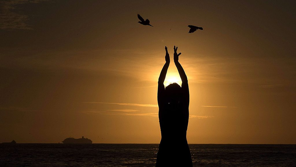 Rio de Janeiro, 2015. december 22.Egy nő nézi a napfelkeltét a déli félteke első nyári napjának hajnalán Rio de Janeiróban 2015. december 22-én. (MTI/EPA/Marcelo Sayao)