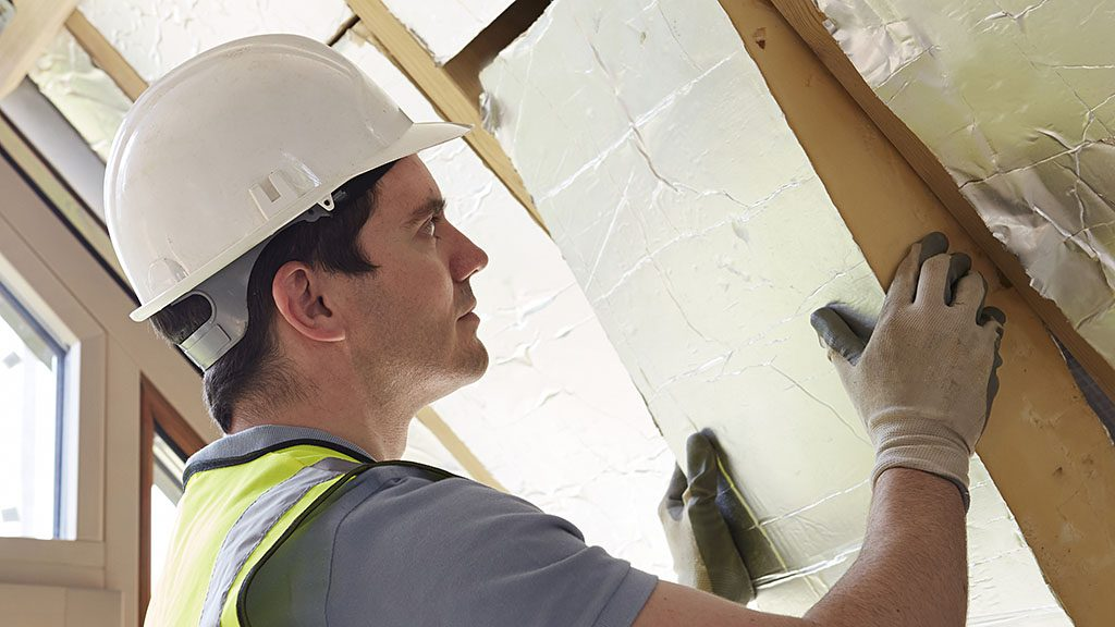 Builder Fitting Insulation Boards Into Roof Of New Home