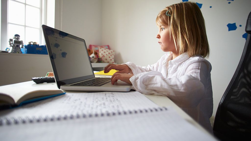 Girl Using Laptop In Bedroom Sitting On Chair Typing On Keyboard