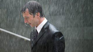 Businessman walking up steps in rain, profile, close-up
