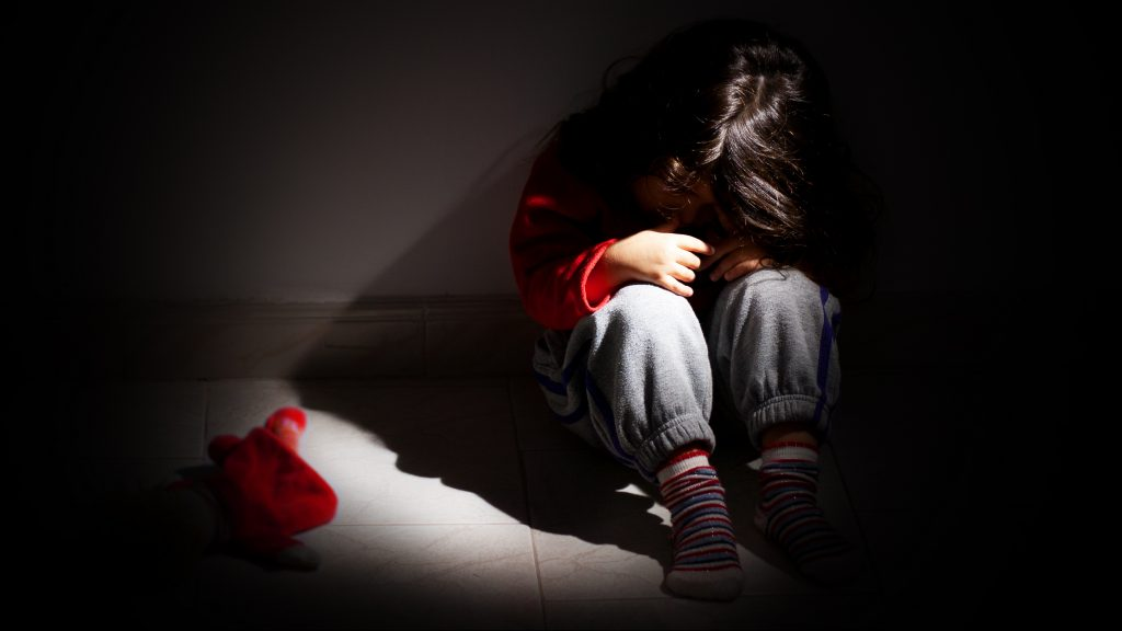 Victim of a child abuse or violence. This photo depicts a child, a young girl, sitting down alone in the dark.  The little girl is sitting on the floor with her head down on her knees. It can represent child (or adult) problems  like loneliness, abandonment, frustration or abuse. Low key photo.