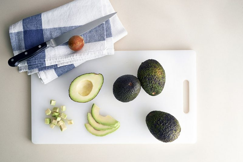 Avocado on chopping block on marble background