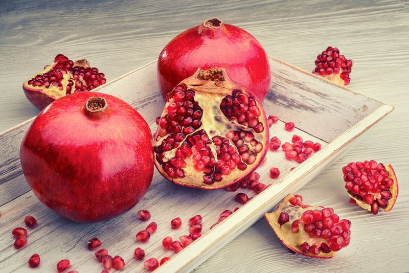 red pomegranate fruits on a white vintage background