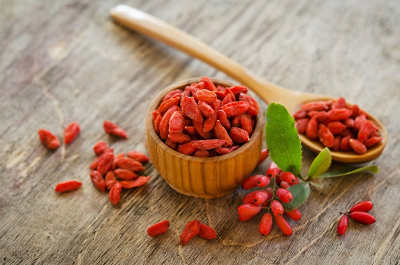 barberries near goji berries heap and wooden spoon, bowl with goji  on wooden background