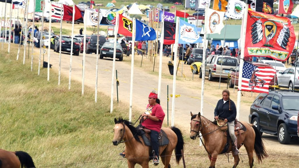 Flags of Native American tribes from across the US and Canada line the entrance to a protest encampment near Cannon Ball, North Dakota where members of the Standing Rock Sioux Tribe and their supporters have gather to voice their opposition to the Dakota Access Pipeline (DAPL), September 3, 2016. Drive on a state highway along the Missouri River, amid the rolling hills and wide prairies of North Dakota, and you'll come across a makeshift camp of Native Americans -- united by a common cause. Members of some 200 tribes have gathered here, many raising tribal flags that flap in the unforgiving wind. Some have been here since April, their numbers fluctuating between hundreds and thousands, in an unprecedented show of joint resistance to the nearly 1,200 mile-long Dakota Access oil pipeline. / AFP PHOTO / Robyn BECK