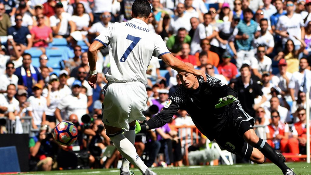 Real Madrid's Portuguese forward Cristiano Ronaldo (R) scores past Osasuna's goalkeeper Nauzet Perez during the Spanish league football match Real Madrid CF vs CA Osasuna at the Santiago Bernabeu stadium in Madrid on September 10, 2016. / AFP PHOTO / GERARD JULIEN