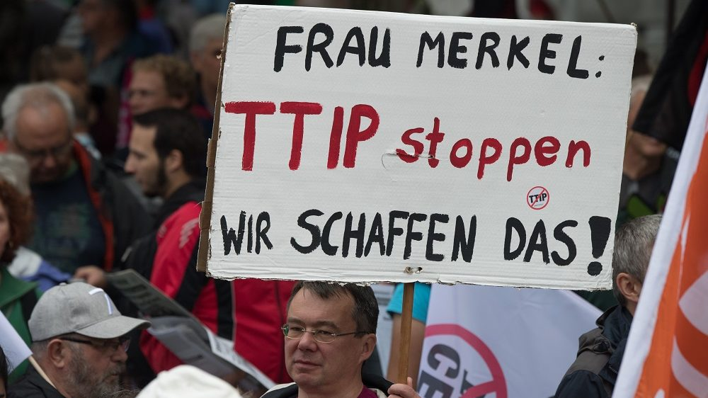 A participant carries a sign written with 'Ms. Merkel: stop TTIP - We can do it!' at a nationwide demonstration against the TTIP and Ceta trade agreements in Frankfurt am Main,Germany, 17 September 2016. Photo:BORISROESSLER/dpa
