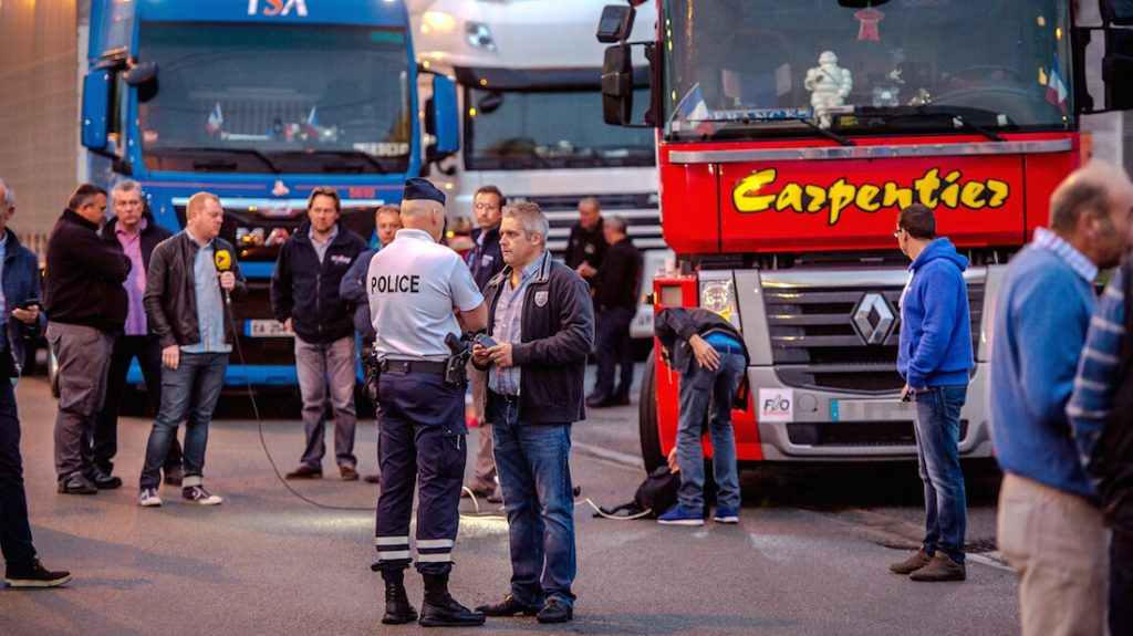 """A man speaks with a police officer as a dozen of truck drivers gather in a parking on September 5, 2016 in Loon Plage prior to a slow-down operation on the A16 highway to ask for the dismantling of the so-called """"Jungle"""" migrant camp in the French northern port city of Calais. / AFP PHOTO / PHILIPPE HUGUEN"""